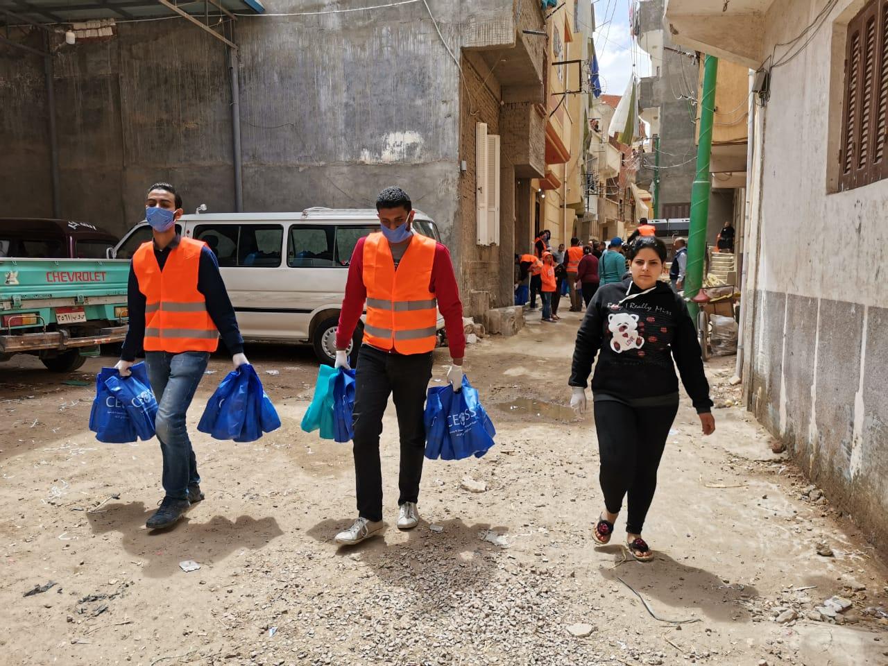الشباب المتطوعين أثناء توزيع حقائب ادوات الوقايه على أهل قرية الأربعمائه